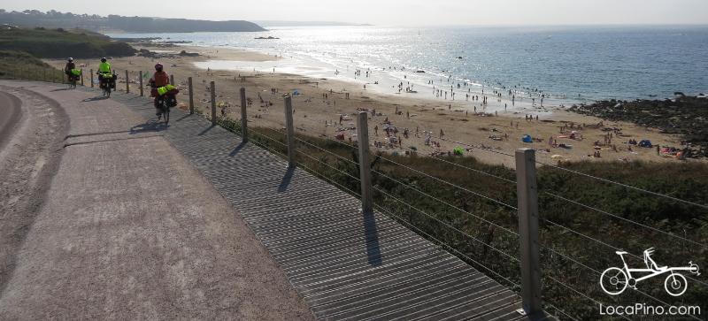 Randonneurs à vélo en Bretagne sur l'Eurovélo 4, au dessus d'une plage