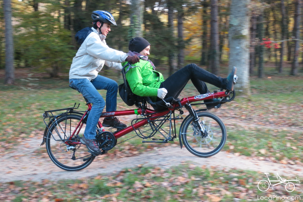 Two people playing with a Pino semi recumbent tandem bike in a forest in France during the fall period