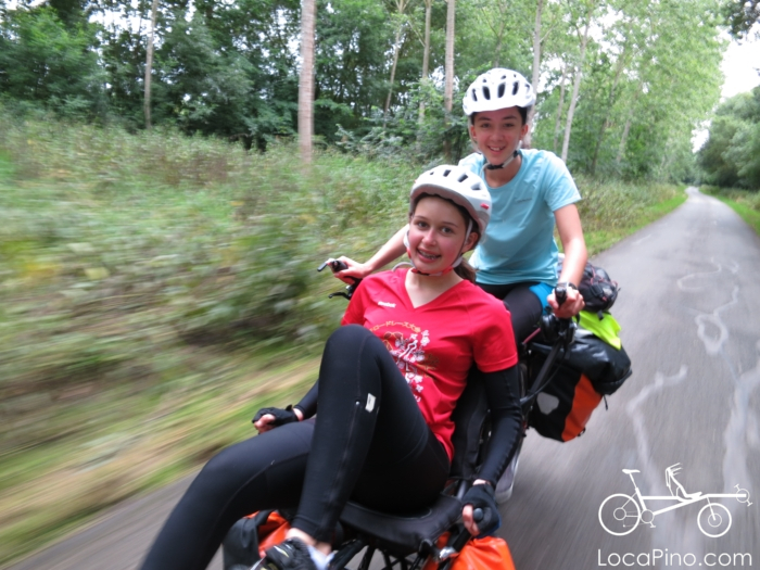 Two teenagers happy to be on the Hase tandem bike on holiday