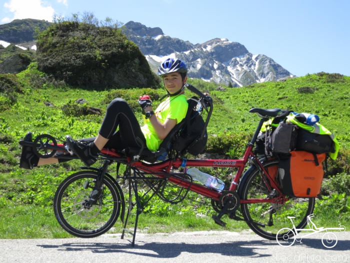 A child in the front seat of a Hase Pino tandem bike when crossing the Alps through the Route des Grandes Alpes, the greatest passes road through the French Alps, when climbing Cormet (Col) de Roselend